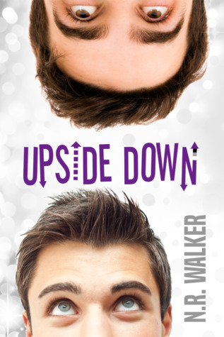 The cover for Upside Down by N.R. Walker. Two men's heads are shown from the nose up, one fight side up from the bottom and one upside down from the top. Both are white men with dark hair, but the top one had brown eyes while the bottom has green, They are looking at each other. The title is in the center in stylized purple text over a white background with confetti-like dots of lights out of focus. The author's name is in grey text vertically in the lower left corner.